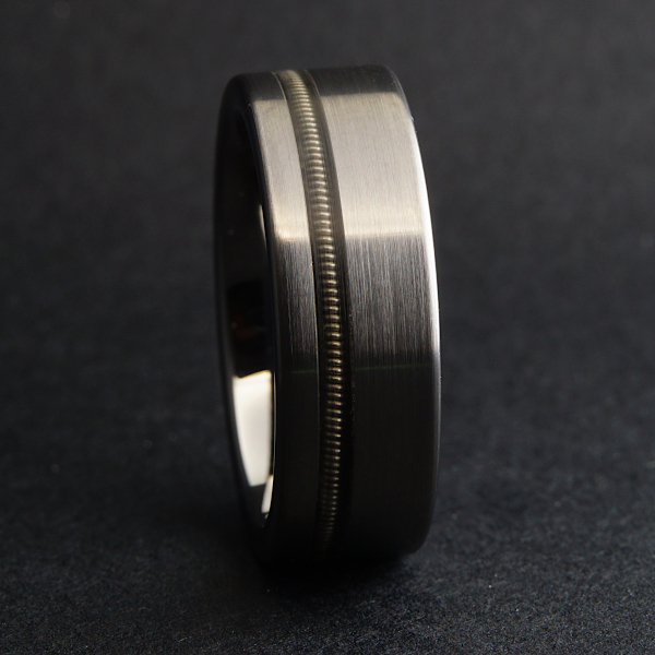 A tungsten ring with an inlaid guitar string on a dark background.
